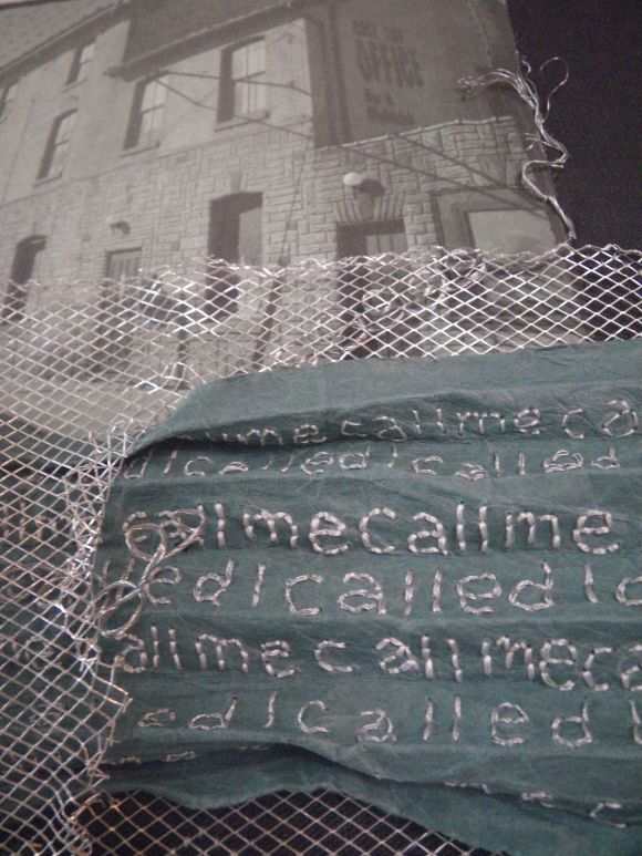 "detail of Missed Call, paper coming though silver mesh fencing; a bar ""Call the Office"" in the background"